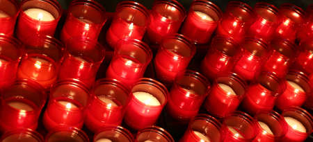 liturgical: many red flames of candles lit by the faithful in the place of worship during the religious ceremony