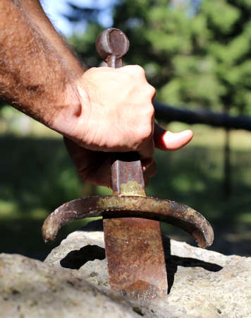 hand of a blockbuster Knight and the Excalibur sword in the stone