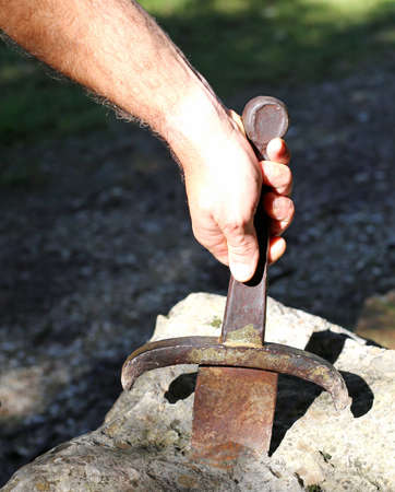 Excalibur sword in the stone and the hand of man in th wood Stock Photo