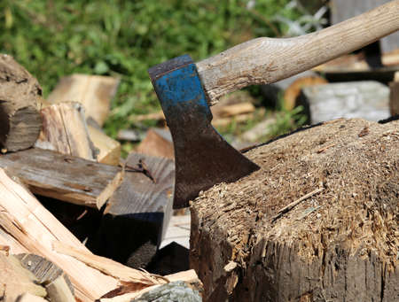 woodshed: big broad ax of the woodcutter on the block of wood in the woodshed