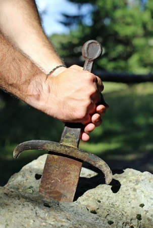 Excalibur sword in the stone and the hands of man