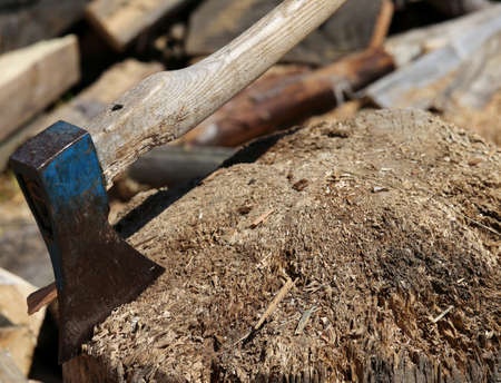woodshed: big ax of a woodcutter on the block of wood in the woodshed Stock Photo
