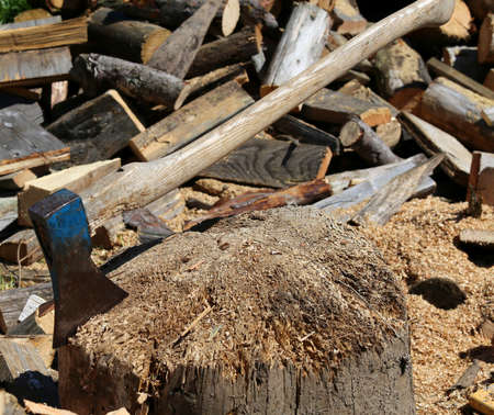 woodshed: big ax of the woodcutter on the block of wood in the woodshed