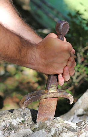 hand of a blockbuster Knight and the famous Excalibur sword in the stone