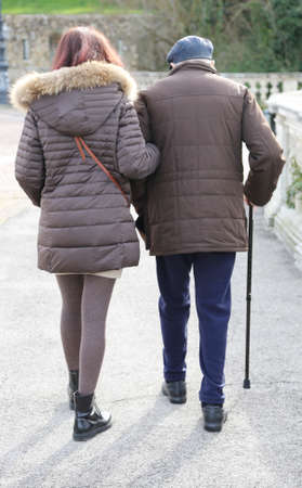 caring daughter walk together to the elderly father walking with stick Stock Photo