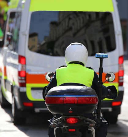 police motorbike with siren on the road with ambulance during an emergency