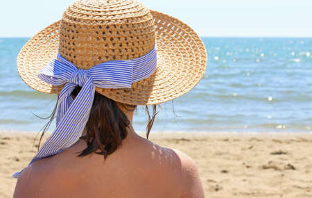 beach babe: Young girl with straw hat by the beautiful sea in summer