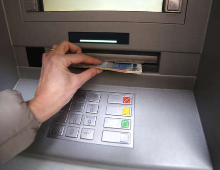 bancomat: hand of young woman while getting euro money from atm bank