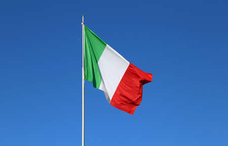 huge Italian flag with the colors red white and green and the blue sky