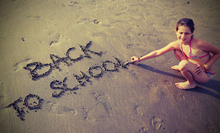 beach babe: babe writes the Back to School on the beach in summer Stock Photo