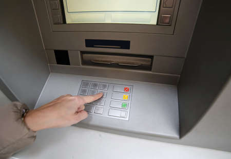 bankomat: hand of woman while enter the secret code in the door of the automatic cash machine