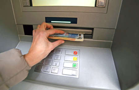 bankomat: woman while she getting money from ATM