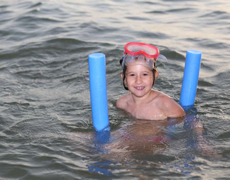 diving mask: smiling little girl plays with the floating plastic tube and diving mask Stock Photo