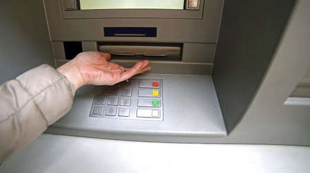 bankomat: hand of woman while waiting the money from atm bankomat