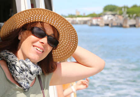 Smiling young woman with straw hat and sun glasses on the ship while traveling
