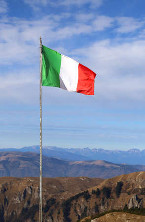 big Italian flag with the colors red white and green svontola high above the mountains