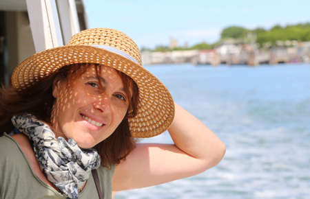 cruising: Smiling beautiful woman with straw hat while cruising in the sea