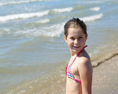 portrait of pretty little girl with a bathing suit on the beach in summer