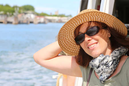 Smiling beautiful woman with straw hat and sun glasses on the ship while traveling