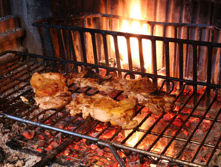 meat grill: cooking the meat grilled chicken in the large fireplace in the restaurant Stock Photo