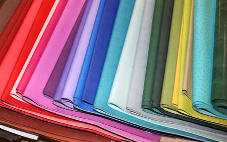 faux: many pieces of colored faux leather for sale in the wholesale of a textile warehouse Stock Photo