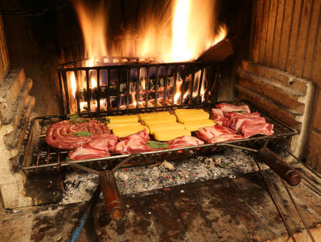a lot of raw meat cooking in the fireplace with a warm fire Stock Photo