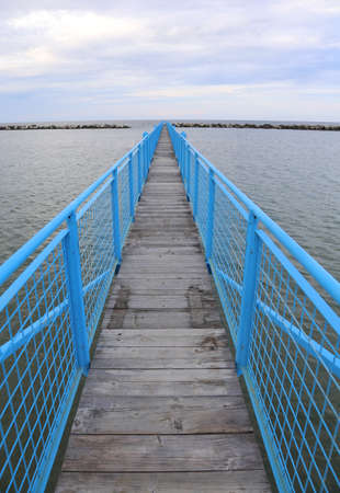 long blue bridge to dock ships at hte sea