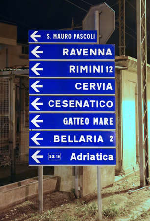 a nocturne: road sign with the indication of the most important seaside resorts of the Adriatic Coast in Italy