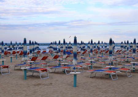 many closed umbrellas in late summer at the beach