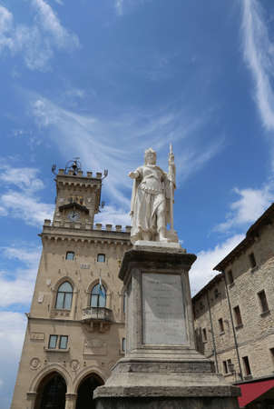 Warrior of marble called Statue of Liberty in San Marino Country and the ancient palace called Palazzo Pubblico seat of Government in Central Italy Editorial