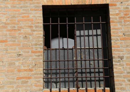 rejas de hierro: ventana rota de una casa abandonada con barras de hierro
