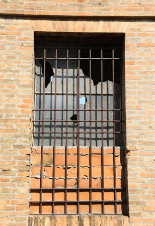 old window of an abandoned house with iron bars