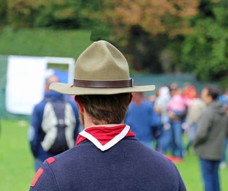 scout leader at international gathering in uniform with campaign hat and scarf red and white