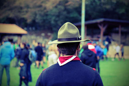 scouting: scout leader at the gathering of young people in uniform with hat and scarf red and white Stock Photo