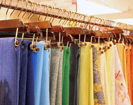 many hangers with woven fabrics and tablecloths on sale
