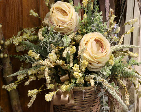 ornamentations: two white roses in a floral decoration in a wicker basket