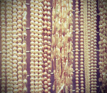 luxuriously: Many beautiful shimmering pearl necklaces for sale in jewelery shop