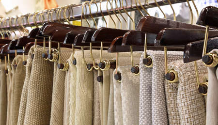 many hangers with woven fabrics and tablecloths on sale in the haberdashery