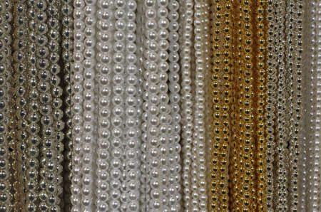 luxuriously: background of precious necklaces of gold beads silver and white for sale