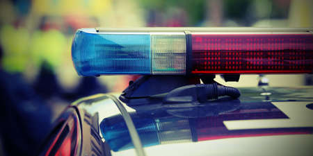 赤と青のチェックポイントで、街で警察の車のライトが点滅します。
