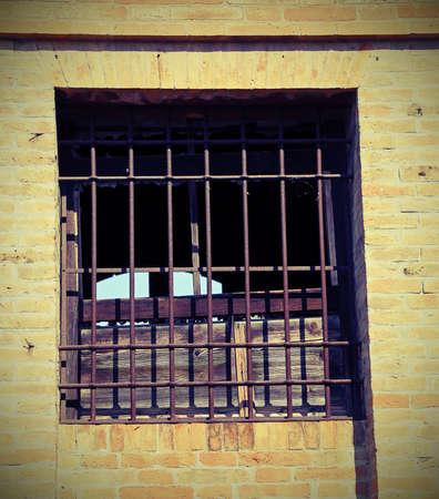 rejas de hierro: ventana rota de una casa abandonada con barras de hierro y cristales rotos Foto de archivo