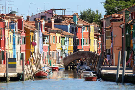 colourfully: Colourfully painted houses and a bridge on Canal in Burano island near Venice in northen Italy Stock Photo