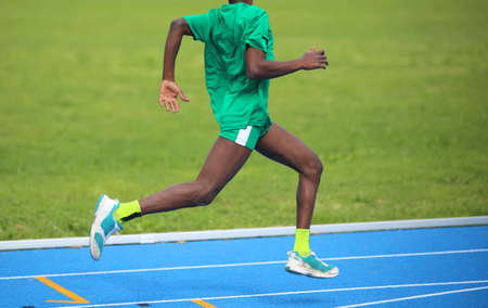 jamaican man: young African athlete won the foot race with long strides and his muscular legs Stock Photo