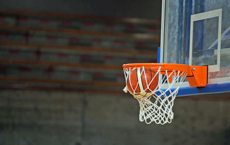 basketball while enters in the basket during basketball game in the sports hall Stock Photo