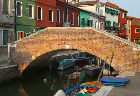 navigable: old brick bridge over the navigable channel island of Burano in northern Italy near Venice Stock Photo