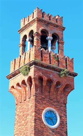 belltower: ancient bell tower on the island of Murano near Venice in northern Italy and blue sky in background Editorial