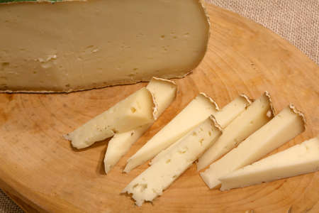 Asiago aged cheese produced in the Italian region of Veneto on a wooden cutting board in the mountain hut Stock Photo