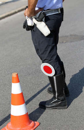 traffic warden: policeman with paddle traffic on the street at checkpoint