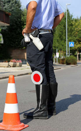 traffic warden: police in a checkpoint while checking motorists and a big traffic cone Stock Photo