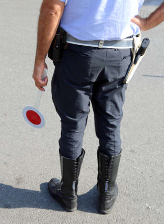 traffic warden: policeman with guns and paddle traffic on the street in checkpoint